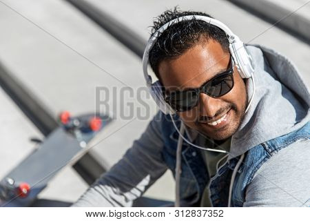 technology, leisure and people concept - indian man in headphones listening to music