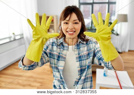 cleaning, housework and housekeeping concept - smiling asian woman with protective rubber gloves on at home