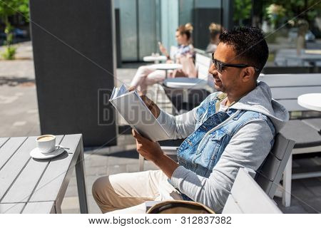 leisure, literature and people concept - indian man reading book with coffee on table at street cafe