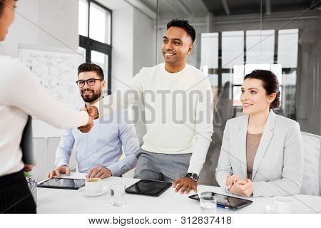 job, hiring and employment concept - international team of recruiters having interview with female employee and shaking hands at office