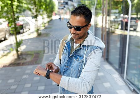 travel, tourism and lifestyle concept - smiling indian man with smart watch and backpack walking along city street