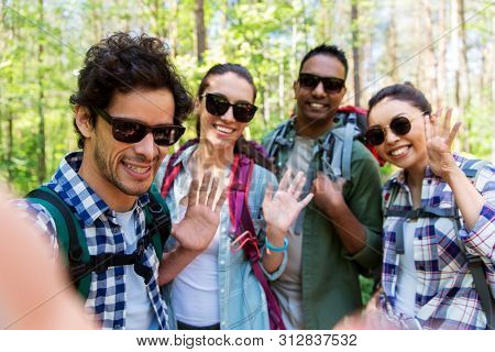 travel, tourism, hike and people concept - group of friends with backpacks taking selfie and waving hands in forest