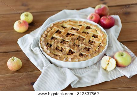 food, culinary and baking concept - apple pie and kitchen towel on wooden table