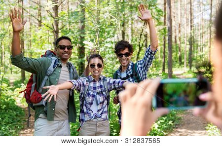 travel, tourism and hike concept - group of friends with backpacks waving hands and being photographed by smartphone in forest