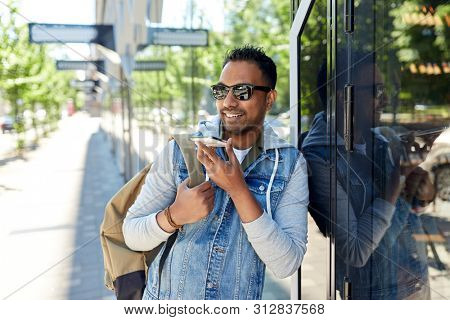travel, tourism and lifestyle concept - smiling indian man with backpack using voice command recorder on smartphone on city street