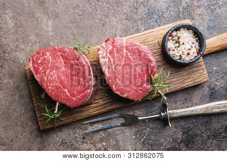 Raw Marbled Meat Steak Filet Mignon With Seasonings Over Stone Background, Top View.
