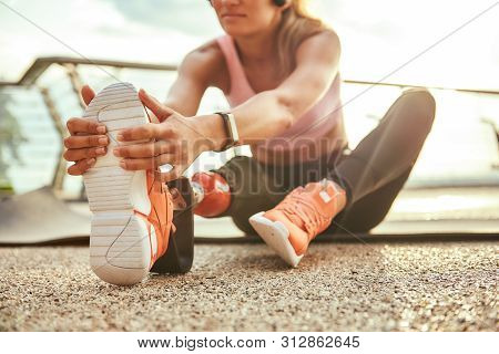 Stretching Exercises. Cropped Photo Of Young Beautiful Woman In Headphones With Leg Prosthesis Liste