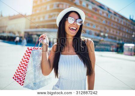 Young Woman In Shopping. Happy Woman With Shopping Bags Enjoying In Shopping.