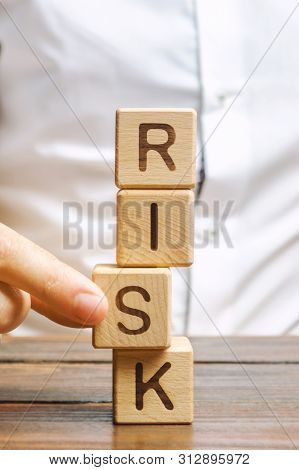 Man Removes Blocks With The Word Risk. The Concept Of Reducing Possible Risks. Insurance, Stability