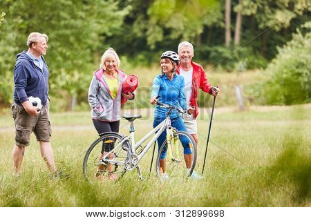 Active seniors in the summer park in a meadow on the way to sports