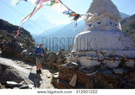 Swedish tourist next to white buddhist stupa on the Everest trek in Himalayas mountains with Ama Dablam mountain on background, Sagarmatha national park, Solukhumbu, Nepal