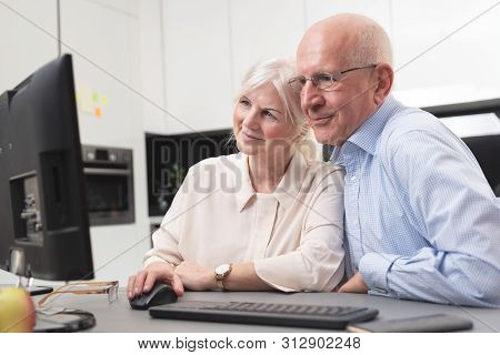 Happy Elder Couple Enjoy Together At Computer. Seniors Use A Computer, They Look At The Pictures The