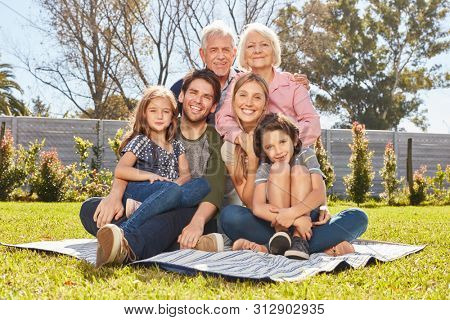 Happy big family with three generations together in the summer in the garden