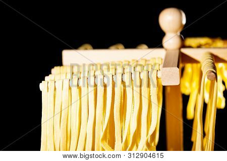 Home Made Tagliatelle Pasta By Pasta Maker Drying On Wooden Sticks Of Pasta Support Frame