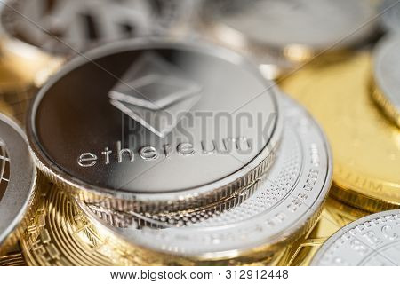 Ethereum Physical Coin On The Stack Of Other Different Cryptocurrencies. Ethereum Cryptocurrency Coi