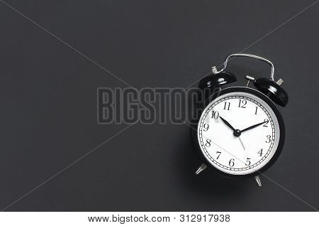 Black Retro Alarm Clock On Gray Dark Background Top View Flat Lay Copy Space. Minimalistic Backgroun