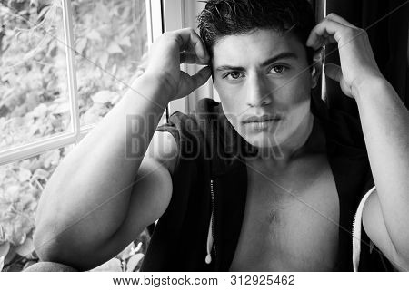 Portrait Of Handsome Latino Man Sitting In Window And Looking At Camera