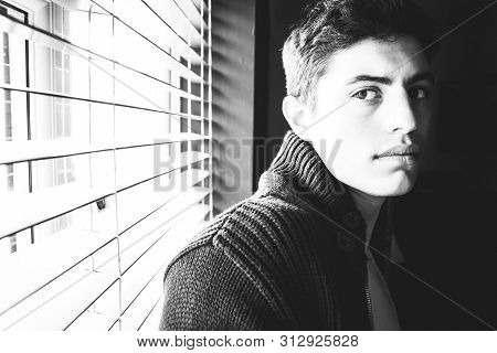 Handsome Latino Man With Pecs Standing In Front Of Window