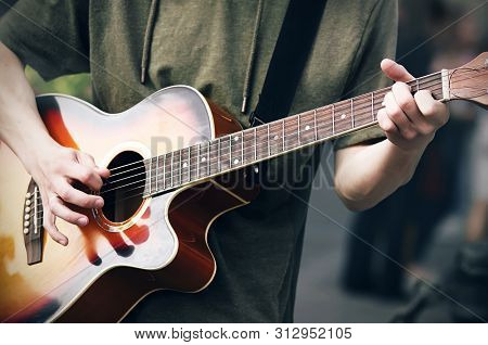 A Young Cocky Guy In A Green Hoodie Plays A Bright Colored Acoustic Six-string Guitar, Holding The C