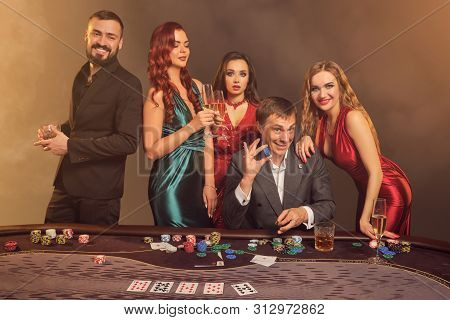 Group of a young wealthy friends are playing poker at a casino. poster