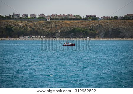 Anapa, Russia - June 17, 2019: Panoramic View Of The Sea Coastwith A Red Ship. On The Left Bay, On T