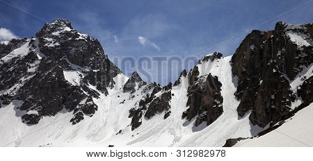 Panoramic View On Snow Covered Sunlit Mountain Range With Traces From Avalanches In Sunny Winter Day