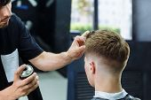 Barber makes hair styling with hair spray after haircut at the barber shop. Young handsome Caucasian man getting a haircut in a modern hairsalon. poster