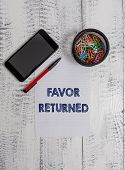 Conceptual hand writing showing Favor Returned. Business photo text Good deed for someone who has done a good deed for you Smartphone paper sheet clips ballpoint wooden vintage background. poster