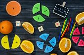 Сolorful math fractions and oranges as a sample on dark wooden background or table. Interesting creative funny math for kids. Education, back to school concept. Geometry and mathematics materials. poster