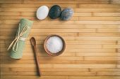 Bath salts natural spa products top view on bamboo wooden texture background with copy space for wellness health concepts. Hot stone massage and exfoliation towel salt in wood bowl. poster