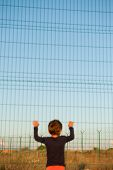 one helpless little child refugee standing near border holding fence with razor wire poster