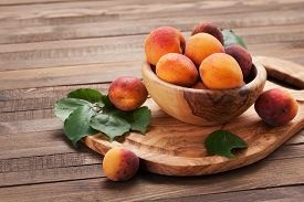 Ripe Apricots In A Wooden Bowl On The Background Of Not Painted Boards Close-up