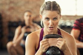 Portrait of concentrated young woman working out with kettlebell at gym. Closeup face of determined girl doing squat session and training biceps. Fitness class lifting heavy weights while squatting.