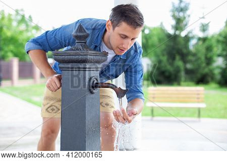 Man Washing His Hand In Faucet Water. Black Column For Distribution Of Drinking Water Installed On S