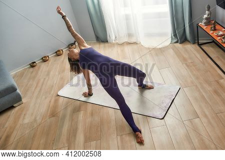 Young Girl Working Out At Home In A Yoga Rack. Beautiful Sportive Girl Working Out At Home On A Yoga