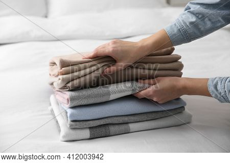 Woman With Folded Cashmere Clothes On Bed, Closeup
