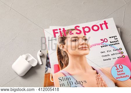 Sports Magazines And Wireless Earphones On Light Grey Table