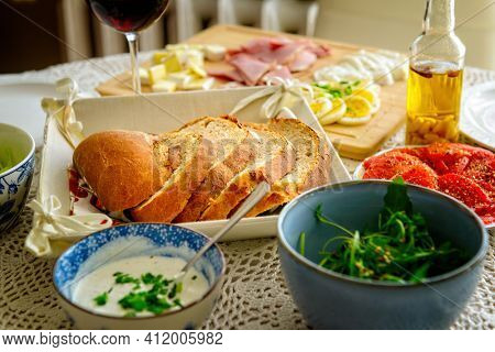 Loaf of bread cut into slices. Continental, healthy breakfast containing homemade bread and a vegetable, cheese and egg, olive, ham Bread based on spelt and rye flour with the addition of wheat flou