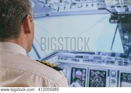 Commercial airplane captain in the cockpit of a flying airplane