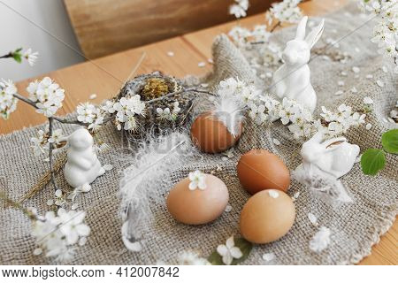 Happy Easter! Natural Easter Eggs, White Bunnies, Feathers, Nest And Cherry Blooming Branch With Pet
