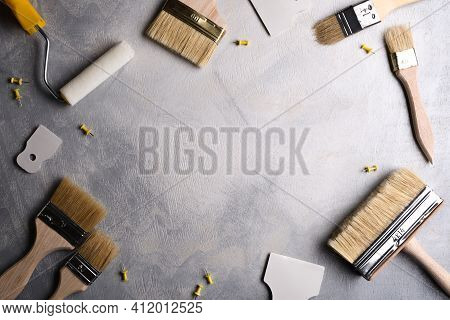 Spatulas For Application Of Putty And Brushes And Rollers For Painting On A Gray Concrete Background