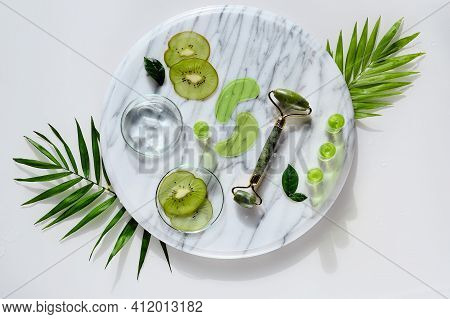 Cosmetic Skincare Background With Kiwi. Stone Roller, Gel Eye Patches. Moisturizing Serum, Ampoule S