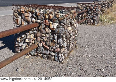 Rocks Stored In A Metal Wire Cubed Cage With Metal Poles Attached Serves As A Boundary Along A Stree