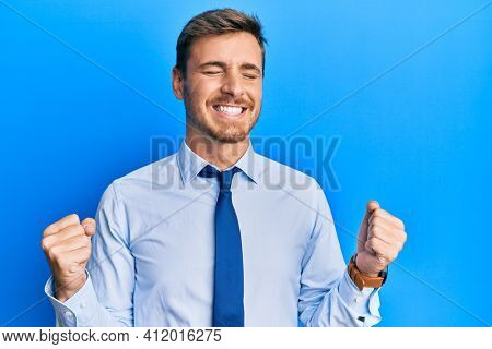 Handsome caucasian man wearing business shirt and tie very happy and excited doing winner gesture with arms raised, smiling and screaming for success. celebration concept.