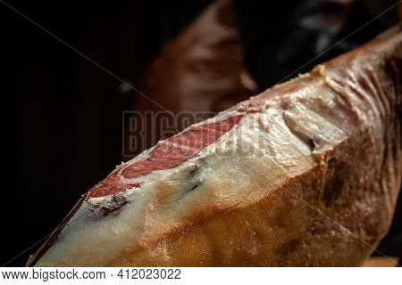 Jamon Serrano. Traditional Spanish Ham, Slicing Of Dry-cured Ham. Iberian Ham Cutter On Black Backgr