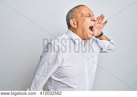 Handsome senior man wearing casual white shirt shouting and screaming loud to side with hand on mouth. communication concept.