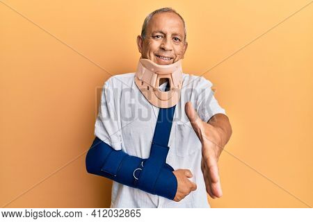 Handsome mature senior man wearing cervical collar and arm on sling smiling friendly offering handshake as greeting and welcoming. successful business.