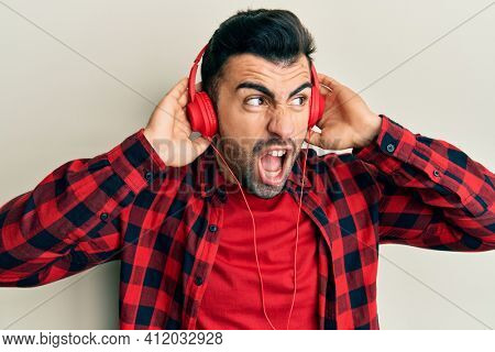 Young hispanic man listening to music using headphones angry and mad screaming frustrated and furious, shouting with anger. rage and aggressive concept.