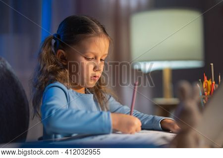 Girl Schoolgirl Junior School Does Homework In The Evening At Home From School. Studying From A Book And Writing In An Exercise Book Sitting At A Table With A Lamp In Her Room
