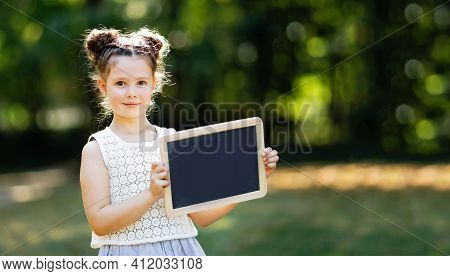 Happy Little Kid Girl Holding Empty Chalk Desk In Hands. Schoolkid On First Day Of Elementary Class.